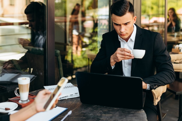 Portrait of businessman holding a cup of coffee and looking at the screen of laptop Premium Photo