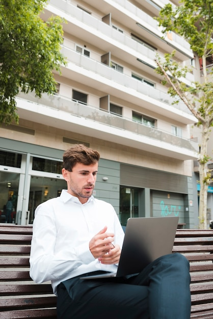Portrait of a businessman looking seriously at laptop in front of building Free Photo