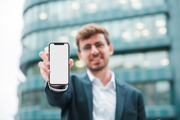 Portrait of a businessman standing in front of building showing mobile phone Free Photo