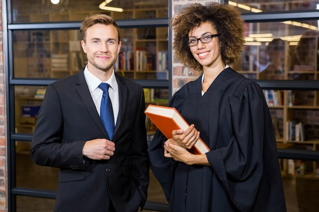 Portrait of businessman standing with lawyer near library in office Premium Photo