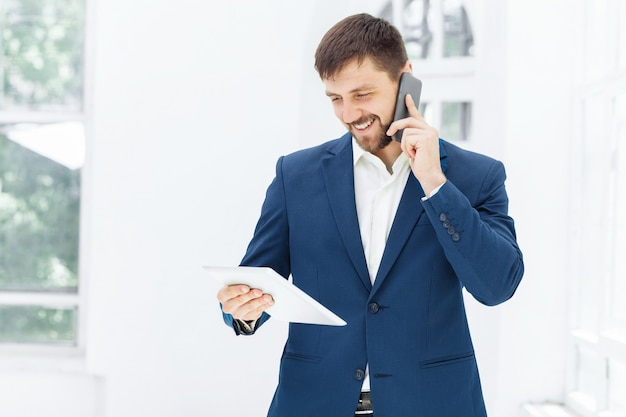 Portrait of businessman talking on phone in office Free Photo