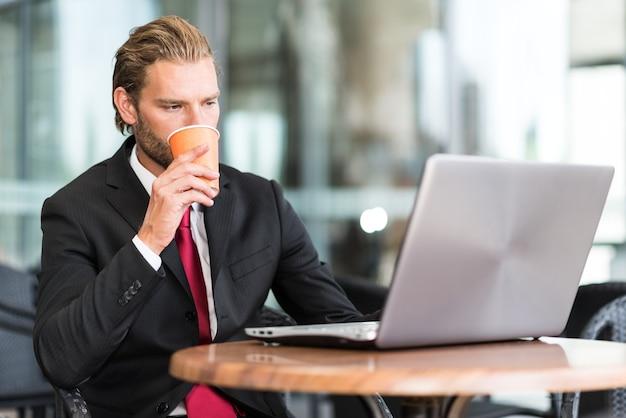 Portrait of a businessman using his laptop computer in a coffee shop Premium Photo