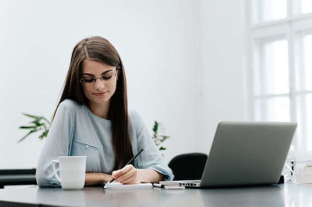 Portrait of businesswoman with laptop writes on a document at her office. Premium Photo