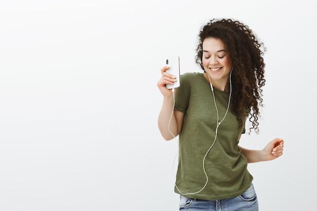 Ritratto di spensierata bella ragazza alla moda con i capelli ricci, ballando con gli occhi chiusi e un ampio sorriso mentre si tiene lo smartphone e ascolta la musica in auricolari Foto Gratuite
