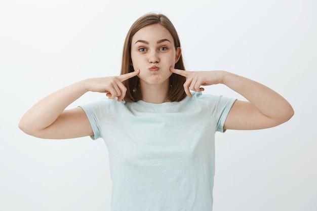 Ritratto di donna europea carina spensierata in maglietta azzurra casual imbronciato, trattenendo il respiro e colpendo le guance con le dita indice divertendosi a passare il tempo sul muro grigio cercando di divertirsi Foto Gratuite