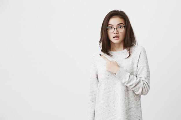 Ritratto di brunetta carina caucasica con gli occhiali, sollevando le sopracciglia in preoccupazione e shock, indicando il dito indice da parte Foto Gratuite