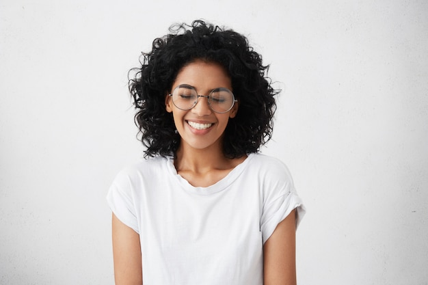 Ritratto di giovane donna africana carismatica e affascinante con capelli ricci che indossano occhiali sylish, sorridendo ampiamente, restringendo gli occhi Foto Gratuite