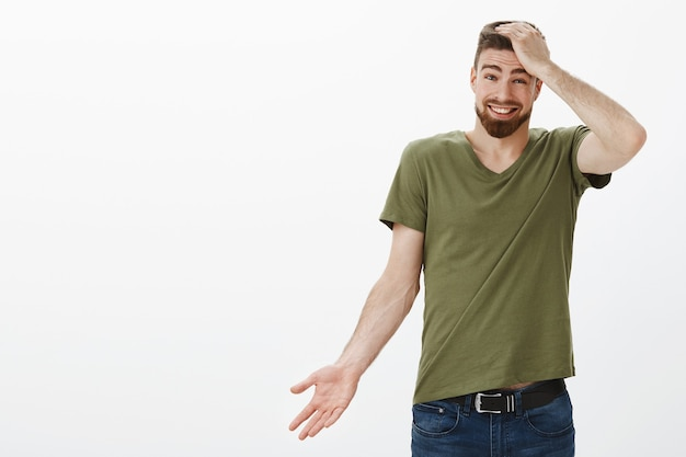 Portrait of charismatic handsome bearded man apologizing for being late, forgetting about time holding hand on head guilty shrugging cute and holding hand sideways, smiling as telling sorry Free Photo