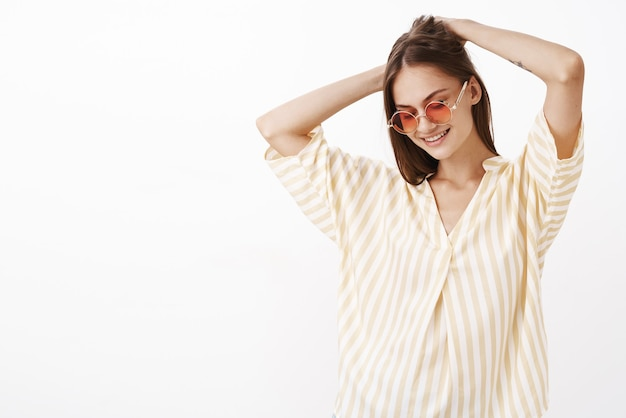 Portrait of charming creative and stylish young female brunette in awesome sunglasses making haircut with hands on head Free Photo