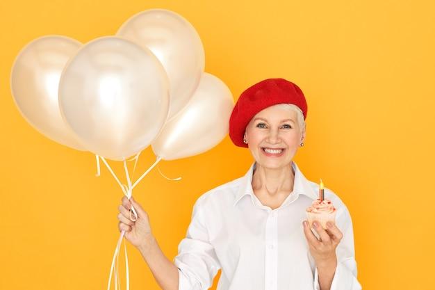 Ritratto di affascinante ed elegante donna in pensione in berretto rosso in posa isolato con palloncini e cupcake compleanno con una candela, esprimendo desiderio, sorridendo felicemente Foto Gratuite
