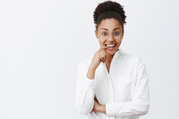 Ritratto di affascinante tutor femminile dalla pelle scura emotiva e femminile in camicia da colletto bianco e occhiali, mordere il dito per curiosità e sorridere ampiamente, guardando incuriosito e interessato Foto Gratuite