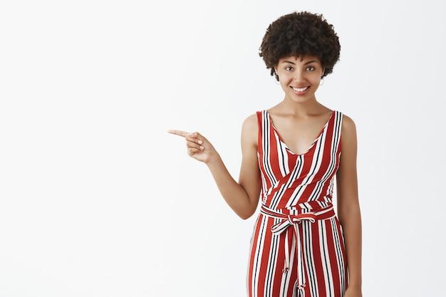Ritratto di affascinante flirty e audace bella donna afroamericana con acconciatura afro che punta a sinistra e sorridente con espressione intrigata e curiosa che mostra interessante spazio di copia Foto Gratuite