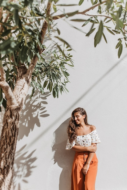 Portrait of charming lady in summer resort outfit posing next to olive tree on white wall Free Photo