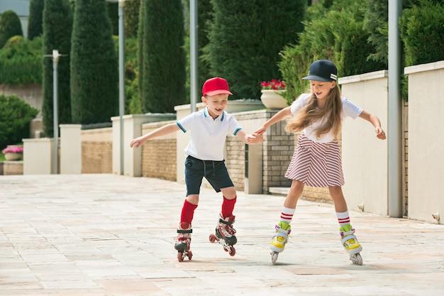 Ritratto di un'affascinante coppia di adolescenti che pattinano insieme sui pattini a rotelle al parco. ragazzo e ragazza caucasici teenager. bambini vestiti colorati, stile di vita, concetti di colori alla moda. Foto Gratuite