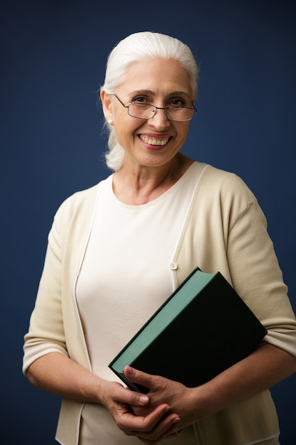 Portrait of cheerful aged woman in glasses, holding book Free Photo