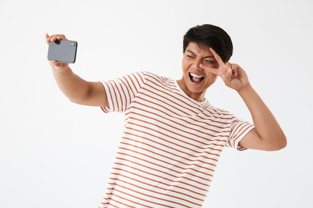 Portrait of a cheerful asian man showing peace gesture Premium Photo