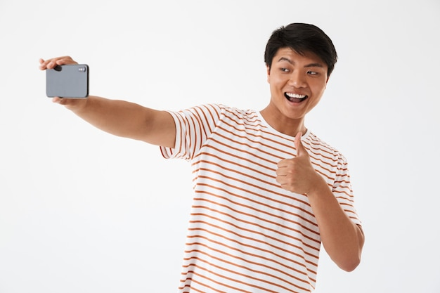 Portrait of a cheerful asian man showing thumbs up Premium Photo