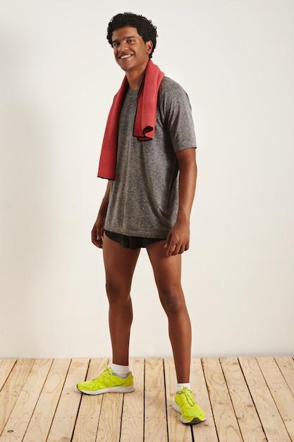 Ritratto di un atleta allegro con un asciugamano rosso sul collo, indossa una maglietta grigia, pantaloncini neri e scarpe da ginnastica verde neon in una stanza con pareti bianche e pavimento in legno chiaro Foto Gratuite