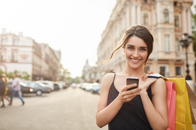 Portrait of cheerful attractive young caucasian woman with dark hair in black dress smiling in camera with teeth, holding shopping bags and smartphone in hands, catting with friend. soft focus Free Photo