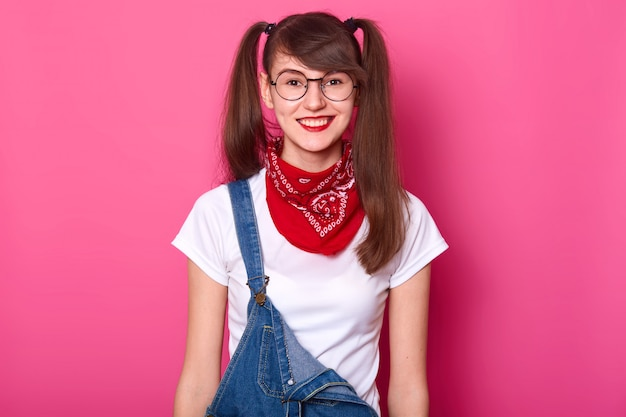 Portrait of cheerful beautiful girl with long pigtails, wears t shirt, denim overalls and red bandana on neck Free Photo