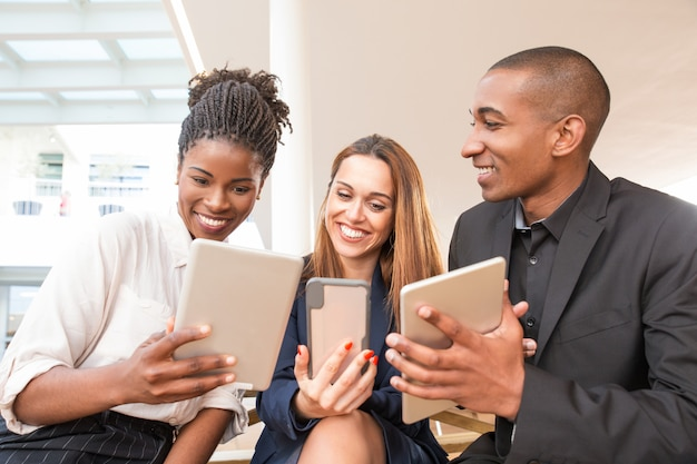 Portrait of cheerful business team using tablets and smartphone Free Photo