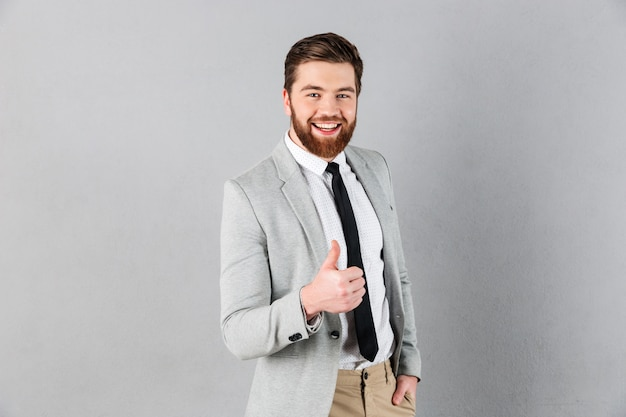 Portrait of a cheerful businessman dressed in suit Free Photo