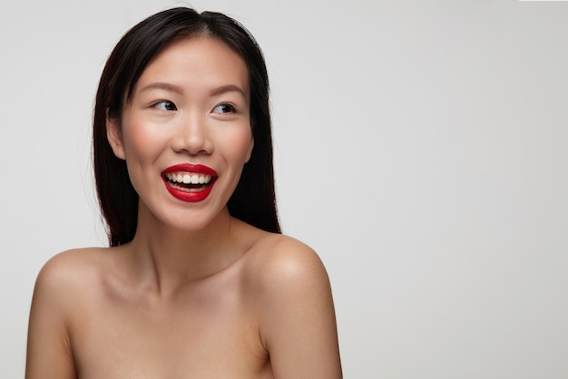 Portrait of cheerful charming young dark haired lady with red lips smiling widely while looking joyfully aside, standing over white wall with naked shoulders Free Photo
