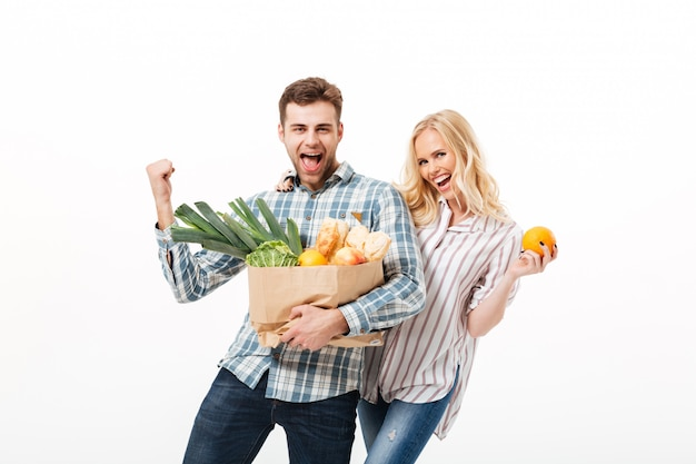 Portrait of a cheerful couple holding paper shopping bag Free Photo