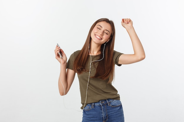 Portrait of a cheerful cute woman listening music in headphones and dancing isolated on a white . Premium Photo