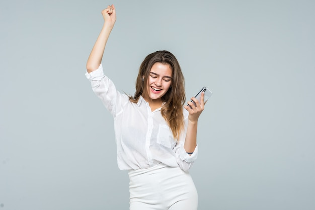 Portrait of a cheerful cute woman listening music in headphones and dancing on a white background Free Photo