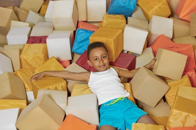 Ritratto del ragazzino afroamericano allegro energico che gioca con i cubi molli nella piscina asciutta Foto Gratuite