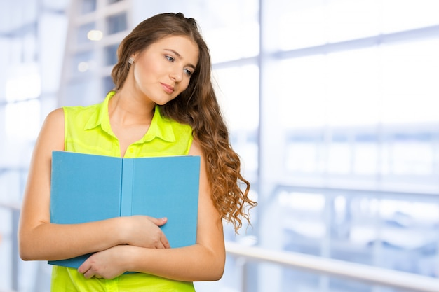 Portrait of a cheerful female teenager with a  book Premium Photo