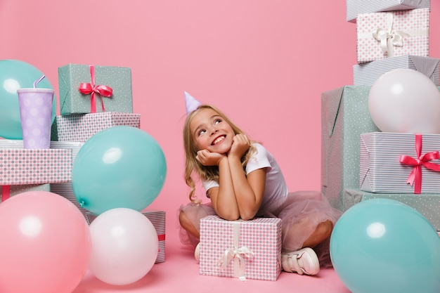Portrait of a cheerful little girl in a birthday hat Free Photo