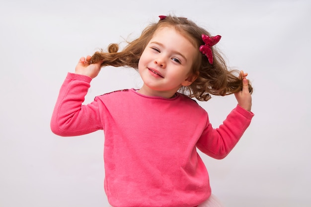 A portrait of a cheerful little girl playing with her hair Premium Photo