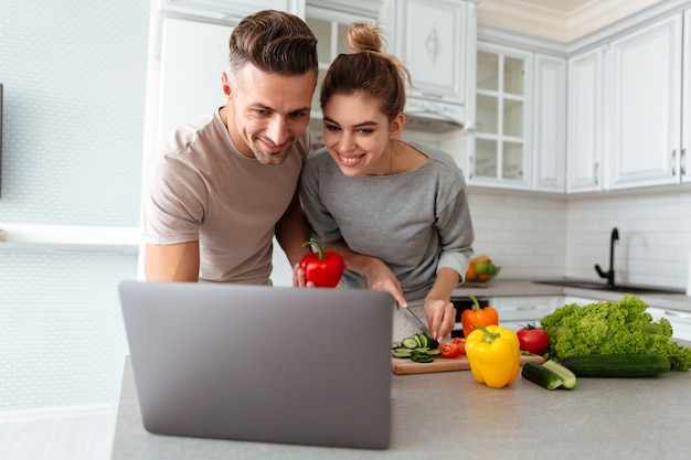 Portrait of a cheerful loving couple cooking salad together Free Photo