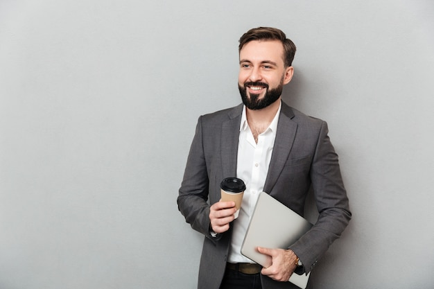 Portrait of cheerful male office worker posing on camera holding takeaway coffee and silver laptop, isolated over gray wall Free Photo