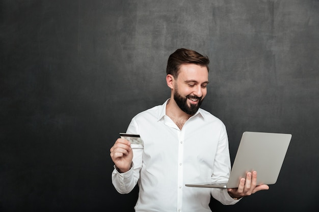 Portrait of cheerful man doing online payment in internet using notebook and credit card, isolated over dark gray Free Photo