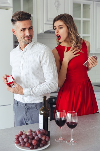 Portrait of a cheerful man proposing to his shocked girlfriend Free Photo