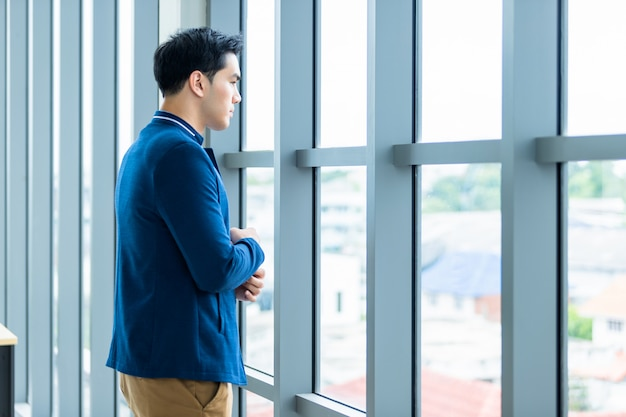 Portrait of a cheerful mature asian young businessman wear a business suit of man in blue jacket and blue shirt looking at the window in the office room. Premium Photo
