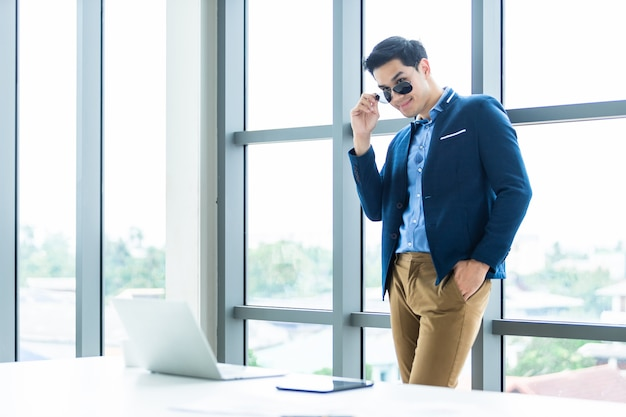 Portrait of a cheerful mature asian young businessman wear a business suit of man in blue jacket and blue shirt  touching his glasses at window in the office room . Premium Photo