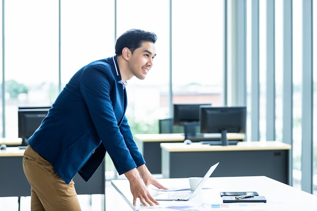 Portrait of a cheerful mature asian young businessman wear a business suit of man in blue shirt and laptop looking at the window in the office room . Premium Photo