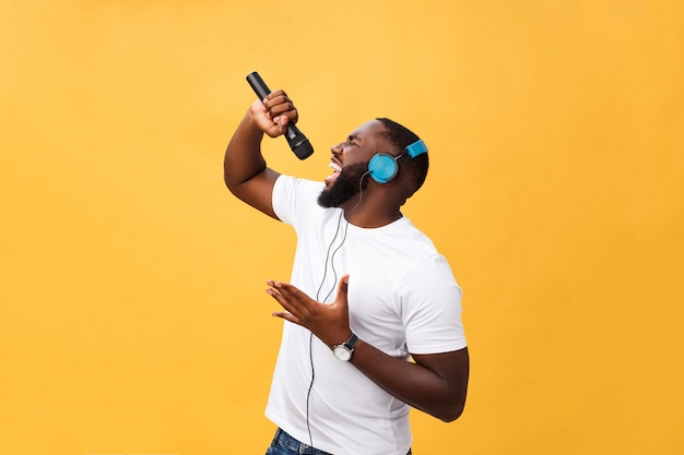 Portrait of cheerful positive chic handsome african man holding microphone and having headphones Premium Photo
