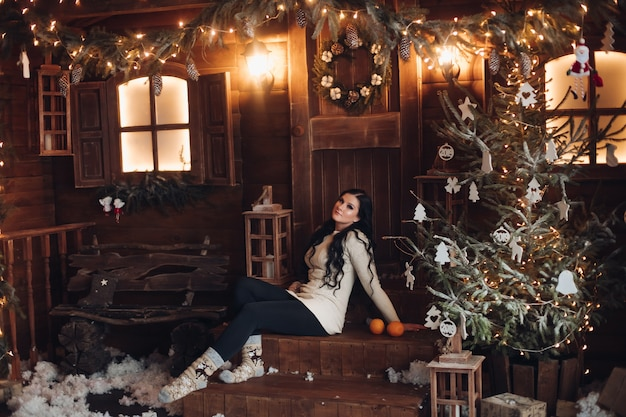 Portrait of cheerful and positive woman with long dark hair in sweater, jeans and warm socks holding wrapped gift for christmas while sitting under decorated christmas tree and snowfall Free Photo