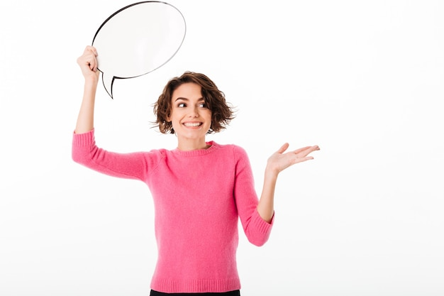 Portrait of a cheerful pretty girl holding blank speech bubble Free Photo