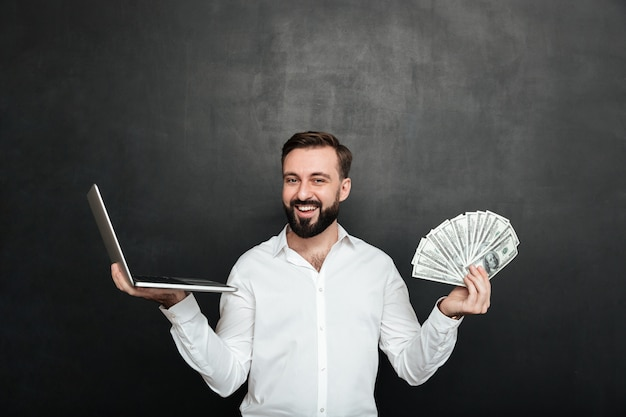 Portrait of cheerful rich man in white shirt winning lots of money dollar currency using his notebook over dark gray Free Photo