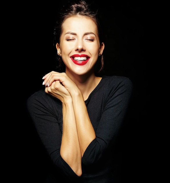 Portrait of cheerful smiling fashion girl in casual black clothes with red lips on black background Free Photo