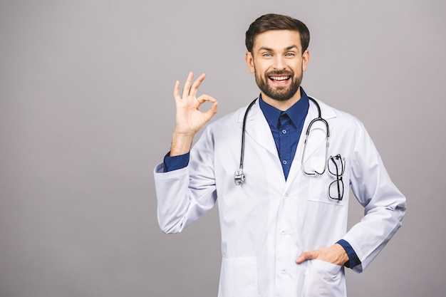 Portrait of cheerful smiling young doctor with stethoscope over neck in medical coat ok sign. Premium Photo