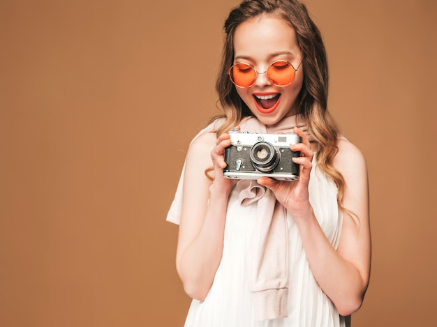 Portrait of cheerful smiling young woman taking photo  with inspiration and wearing white dress. girl holding retro camera. model in sunglasses posing Free Photo