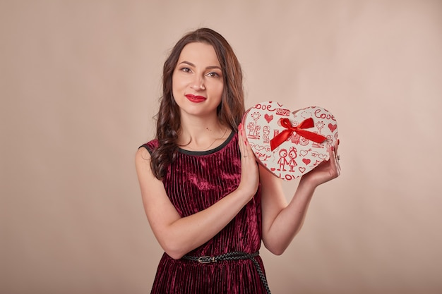 Portrait of cheerful woman in red dress holding gift box Premium Photo