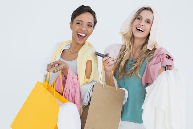 Portrait of cheerful women standing with shopping bags Premium Photo
